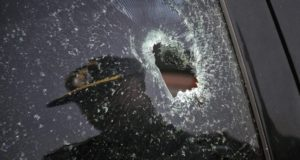 A policeman is reflected in a window of a car shattered by bullets, currently parked in a police station in Karachi