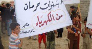 طفلان يرفعان يافطة تنتقد نقص الكهرباء في العراق