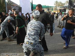 قوات عراقية تقوم بتفتيش الزوار أثناء الاحتفال بذكرى الإمام موسى الكاظم